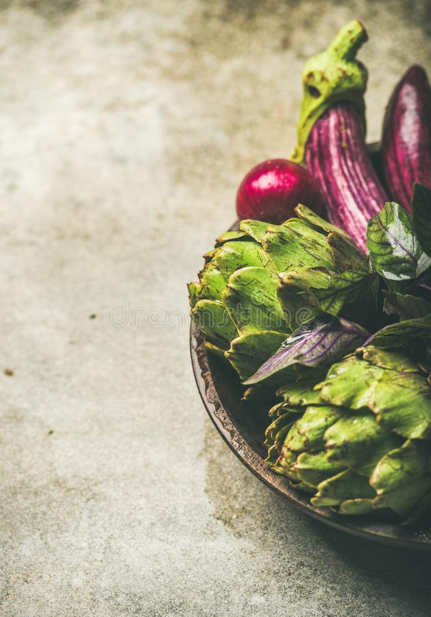 Flat-lay of green and purple vegetables on plate, copy space stock image