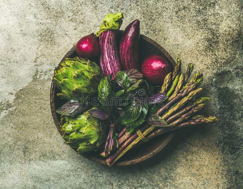 Flat-lay of green and purple vegetables on plate, grey background royalty free stock images
