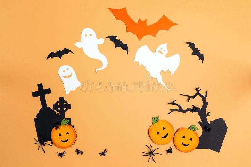 Flat lay Halloween background with cartoon cemetery, pumpkins an. D ghosts. Space for text royalty free stock image
