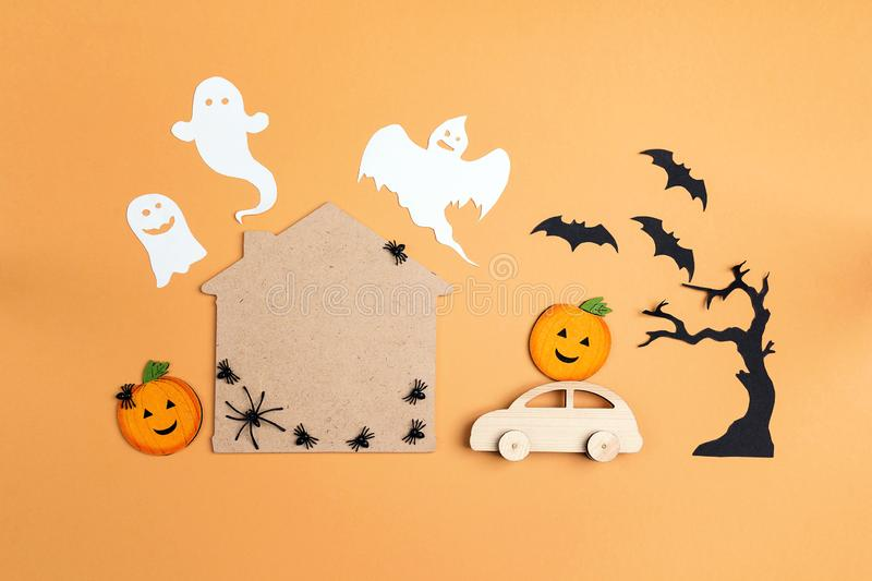 Flat lay Halloween background with cartoon house, car, pumpkins. And ghosts. Space for text stock photo