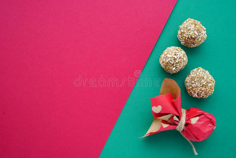 Flat lay handmade coconut round candies on the green and pink rose rosy background with hearts 14 February royalty free stock image