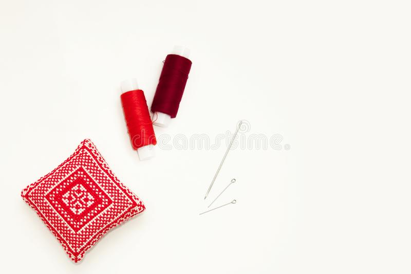 Flat lay with handmade red embroidered needle pad, thread spools, pins, needles, mock up, top view. Layout mockup on blank white stock photography