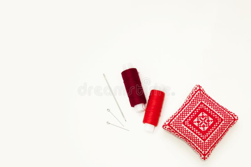 Flat lay with handmade red embroidered needle pad, thread spools, pins, needles, mock up, top view. Layout mockup on blank white stock photo