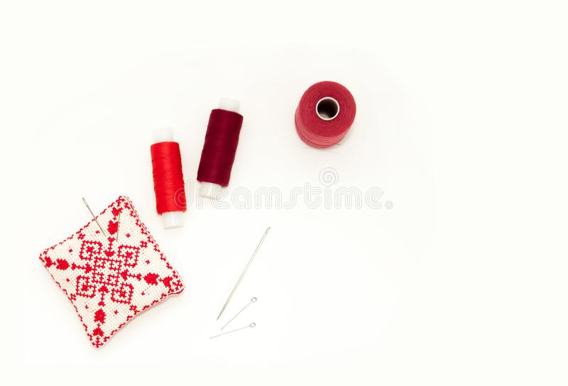 Flat lay with handmade red embroidered needle pad, thread spools, pins, needles, mock up, top view. Layout mockup on blank white stock image