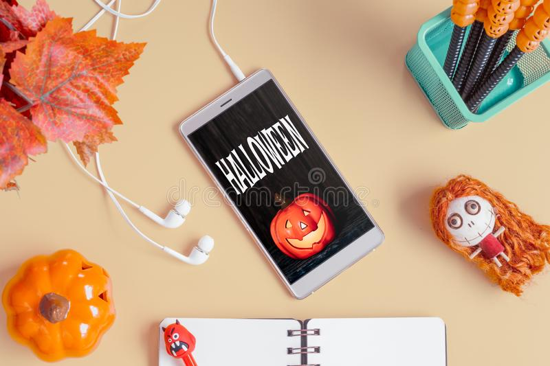 Flat lay Happy Halloween Mobile phone mockup background concept. Top view of smartphone on office desk table with Halloween stock photos