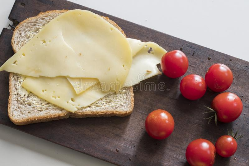 Flat lay healthy breakfast with slice of brown bread, Dutch cheese and tomatoes stock image