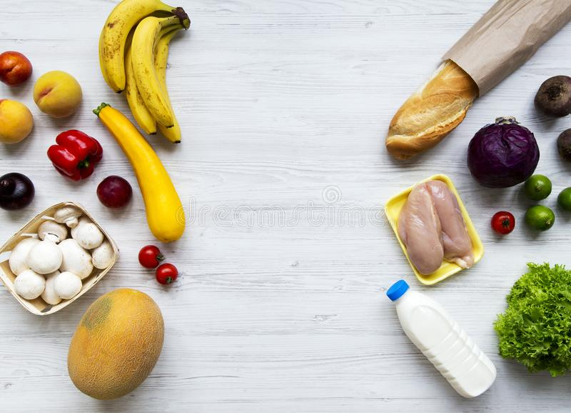 Flat lay of healthy raw food on white wooden table. Cooking food background. Top view, fresh fruits, veggies, greens, meat, milk. stock image