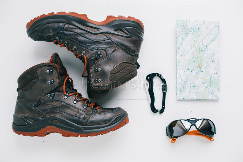 Flat lay of hiking boots, eyeglasses, carabiner and map royalty free stock photo