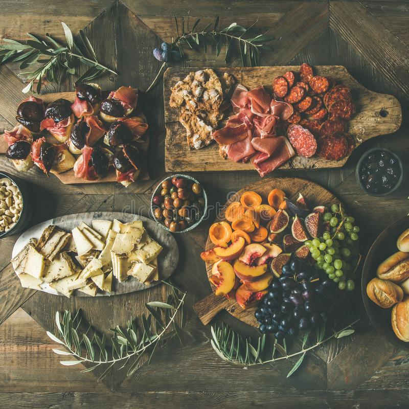Flat-lay of holiday, party, family dinner table set, square crop. Flat-lay of holiday, party, family dinner table set with wine snacks. Meat, cheese, olives royalty free stock photos