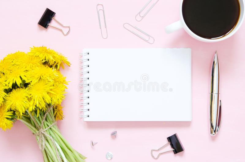 Flat lay home office desk. Female workspace with bouquet of dandelions, notebook, stationery supplies on pink background. stock images