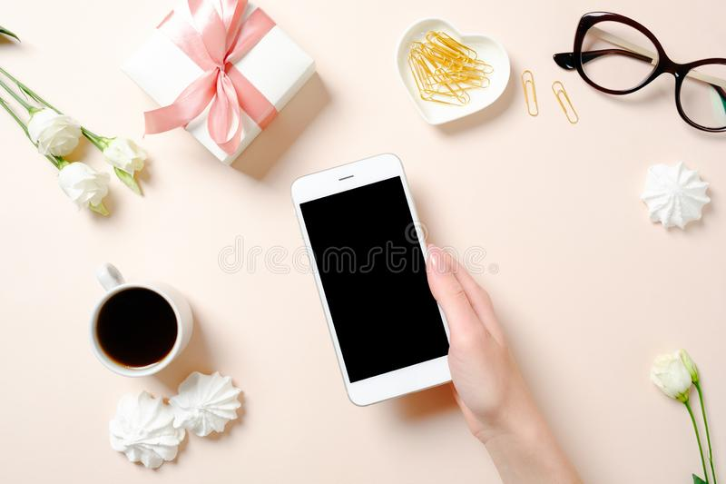 Flat lay home office desk. Female workspace with human hand holding smartphone, coffee cup, glasses, flowers, golden accessories stock images