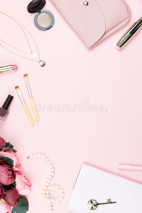 Flat lay home office desk. Female workspace with note pad, fashion accessories and make up products on pink background. Fashion or royalty free stock photos