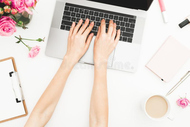 Flat lay home office desk. Woman workspace with female hands, laptop, pink roses bouquet, accessories, diary. Top view. Girl worki royalty free stock photography
