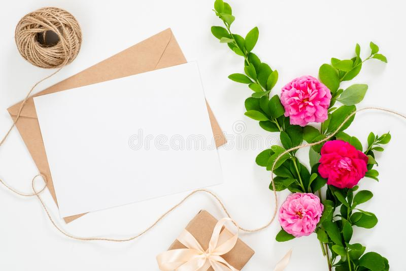 Flat lay home office desk. Women workspace with blank paper card, gift box, bouquet of rose flowers. Top view feminine background royalty free stock photo