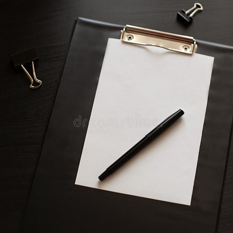 Flat lay home office desk. Workspace with blank black clipboard with a pen and stationery. stock photo