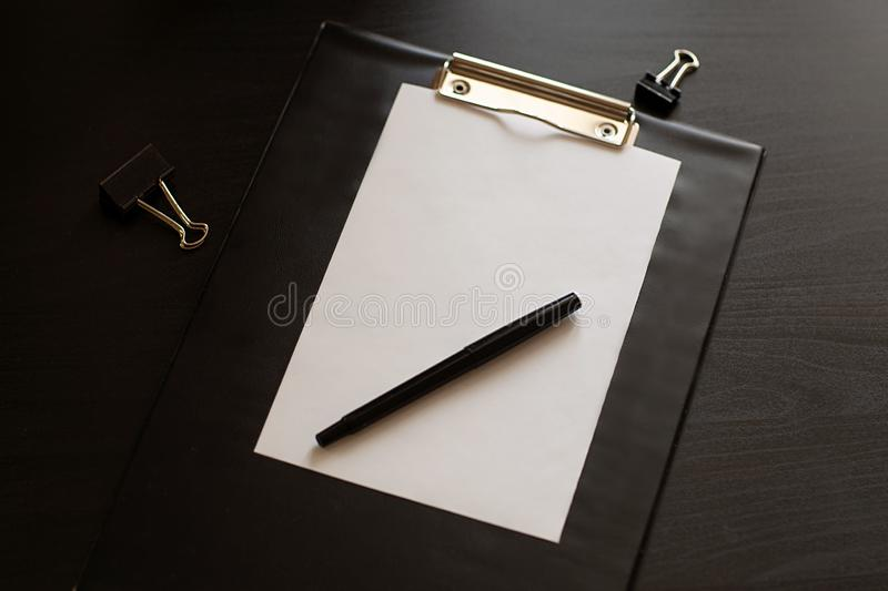 Flat lay home office desk. Workspace with blank black clipboard with a pen and stationery. stock image