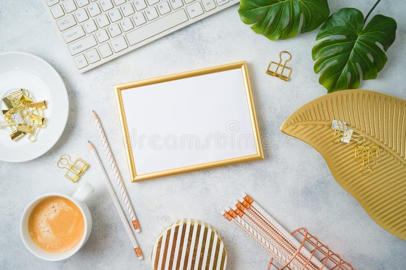 Flat lay home office feminine table with frame mockup, golden accessories, computer keyboard and tropical leaves on grey stock photos