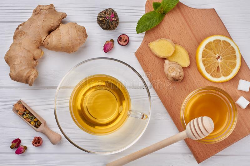 Flat lay honey, lemon, ginger tea. Cup of ginger tea with lemon, honey, ginger root and mint leaves on a white wooden background royalty free stock photos