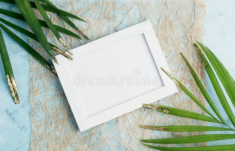 Flat lay horizontal photo frame tropical mock up on craft paper with green and gold palm leaves on blue background. Travel concept royalty free stock image