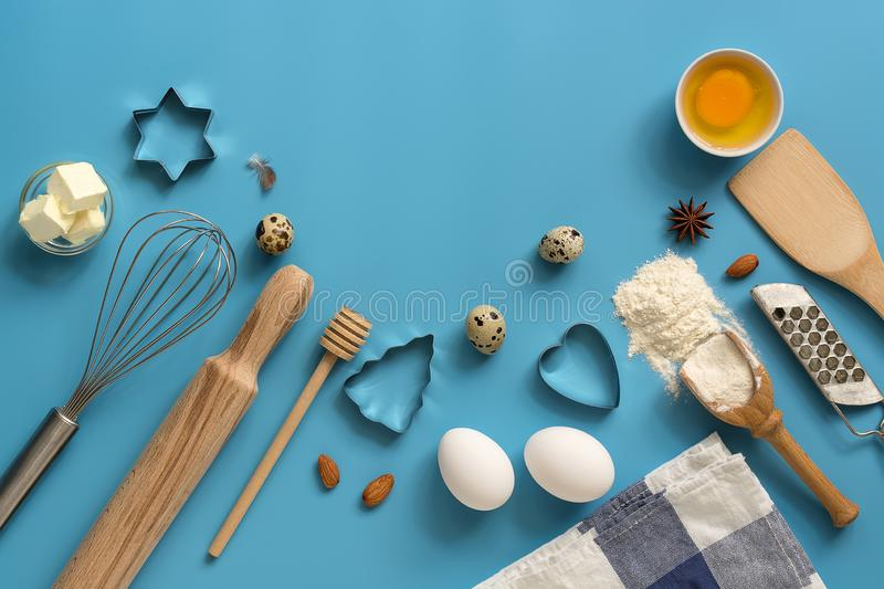 Flat lay ingredients for baking and kitchen utensils on a blue background. Top view, place for your text royalty free stock photography
