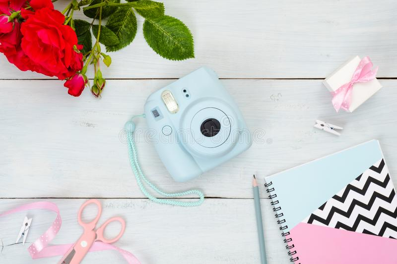 Flat lay Instant film camera and feminine accessories on pastel blue wooden background. Top virw frame set of beuty blogger items royalty free stock photo