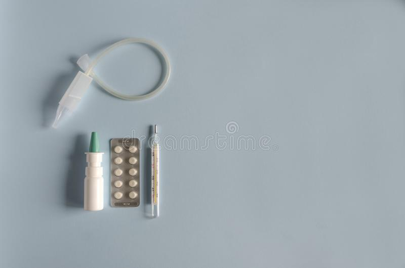 Flat lay instrument for nasal rinsing, mercury thermometer, nasal spray, tablets for the treatment of illness, flu and cold. Soft focus, copy spase stock photography