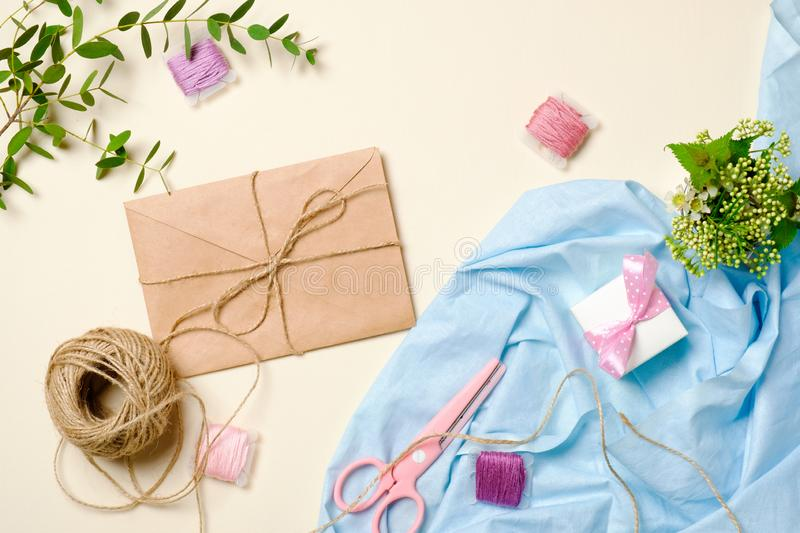 Flat lay kraft paper envelope, blue cloth, pink scissors, twine, green plant on pastel color beige background. Top view woman. Table desk with feminine stock photography
