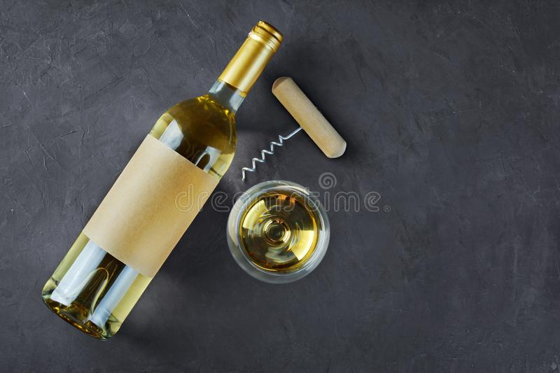 Flat lay of lying white wine bottle with empty label, corkscrew and glass for tasting stock images