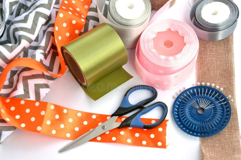Flat lay made by color ribbons, scissors and pins on white background royalty free stock photo