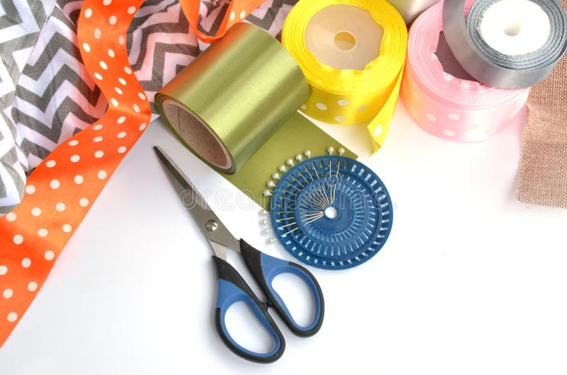 Flat lay made by color ribbons, scissors and pins on white background stock image