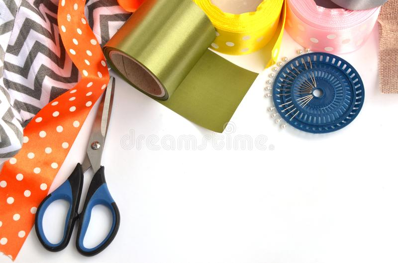 Flat lay made by color ribbons, scissors and pins on white background stock photos