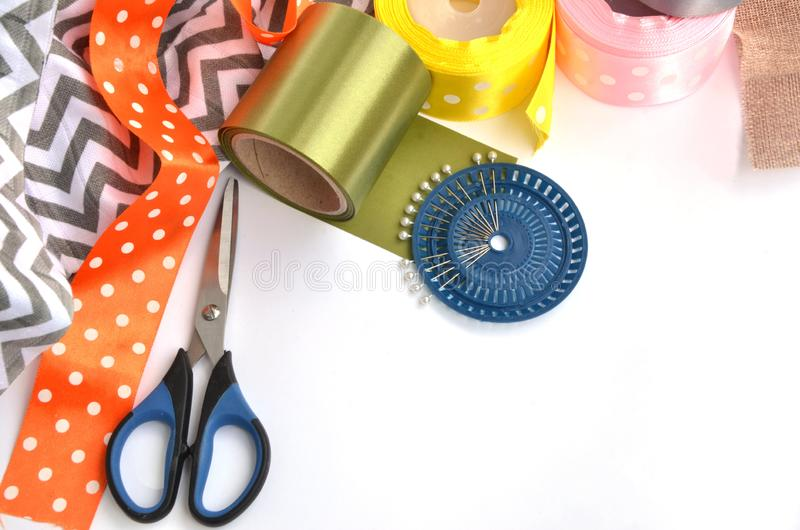 Flat lay made by color ribbons, scissors and pins on white background stock photography