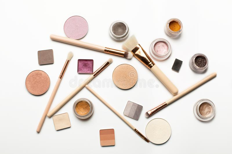Flat lay of makeup brushes, highlighter,cream eyeshadow, brow ge royalty free stock photography