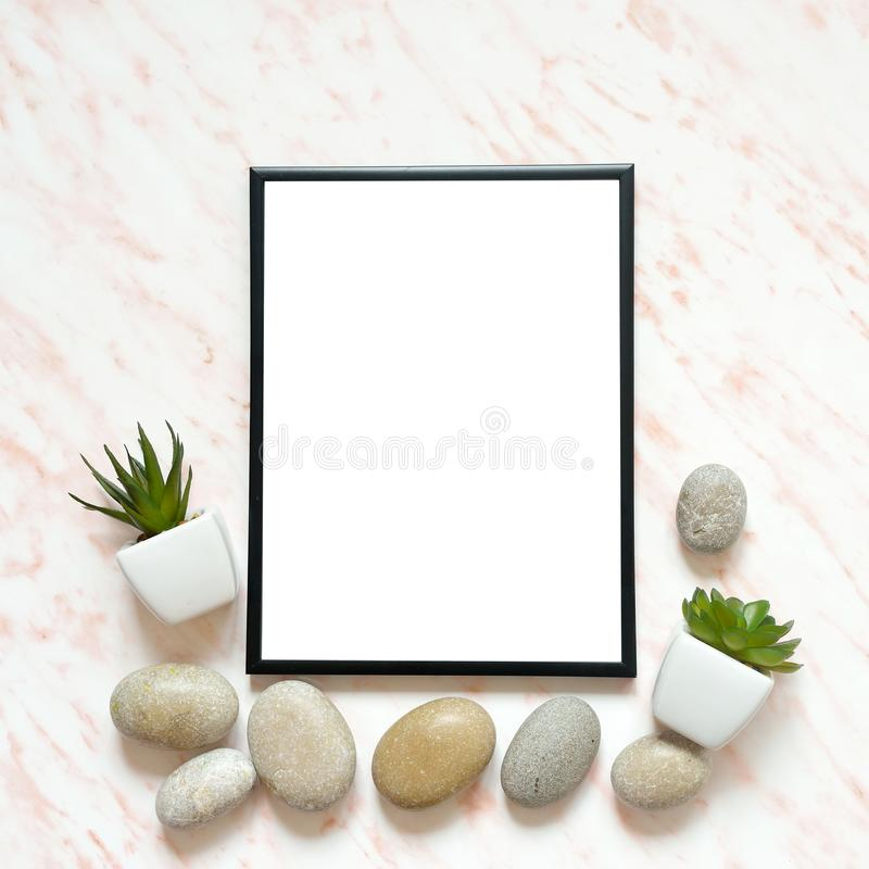 Flat lay marble desk with white empty frame for text, stones and succulents background stock photos