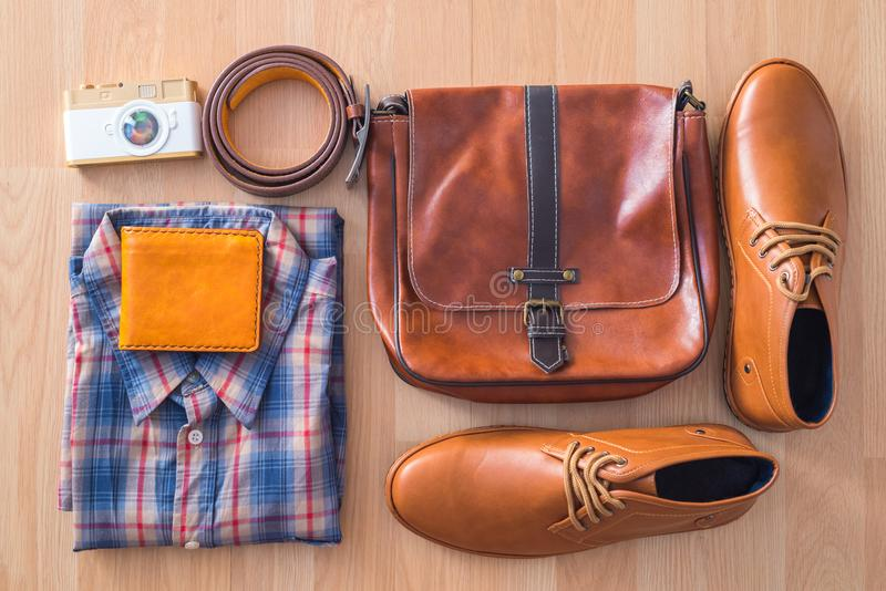 Flat lay of men`s casual fashion on brown wooden floor backgroun royalty free stock photo