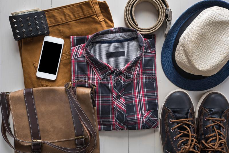 Flat lay of men`s casual fashion set with leather accessories o. N wooden floor royalty free stock photography