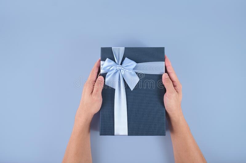 Flat lay of Men`s hand holding decorative dark blue gift box with light blue bow isolated on pastel colored background, Man hand royalty free stock images