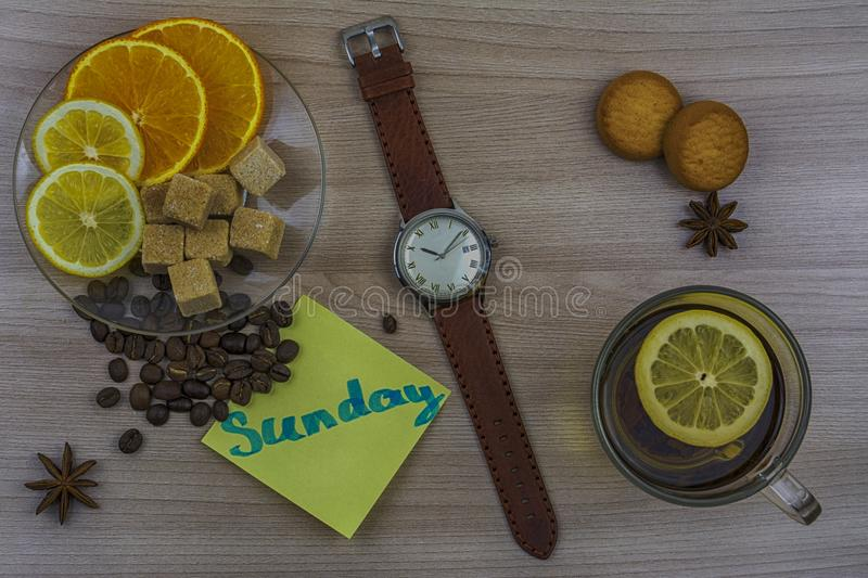 Flat lay. Men`s watches with leather strap. Sticker with inscription Sunday. Cup of tea with lemon. Slices of lemon and orange on royalty free stock photos