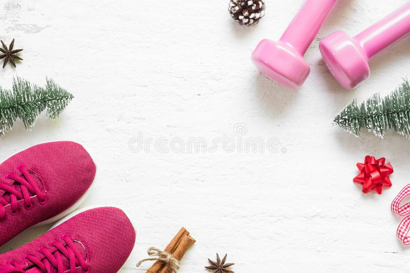 Flat lay of Merry Christmas and Happy new year for healthy and a. Ctive lifestyle concepts. Composition with dumbbells, sport shoes and Christmast decoration on stock photo