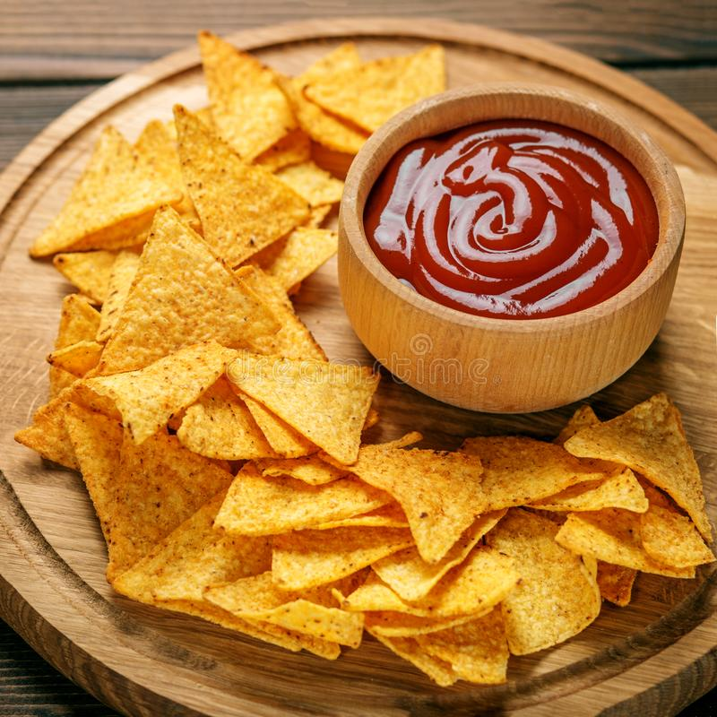 Concept Bad flat lay nachos chips with spicy tomato sauce concept