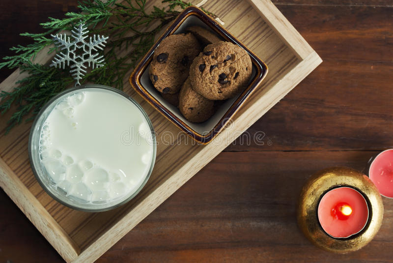 flat lay milk and chocolate chip cookie with snowflake and candle on wood royalty free stock photos