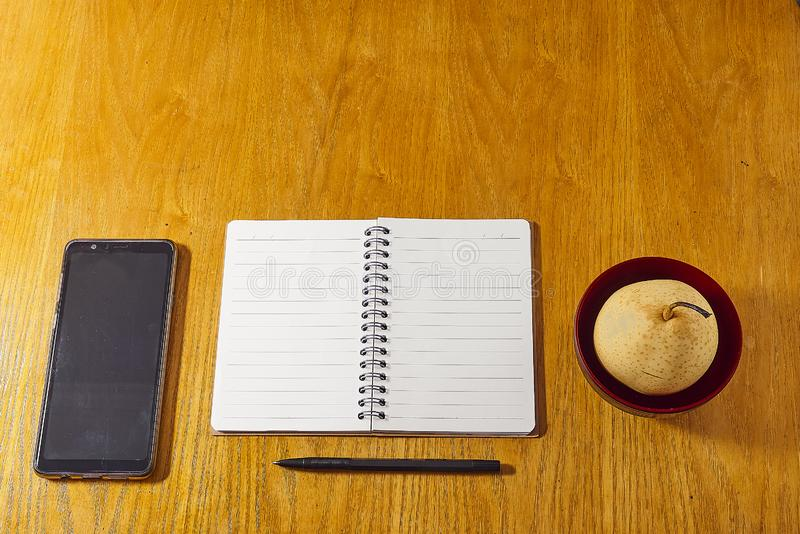 Flat lay minimalistic work place. Wood office desk table with notebook, pen and a fruit stock photo