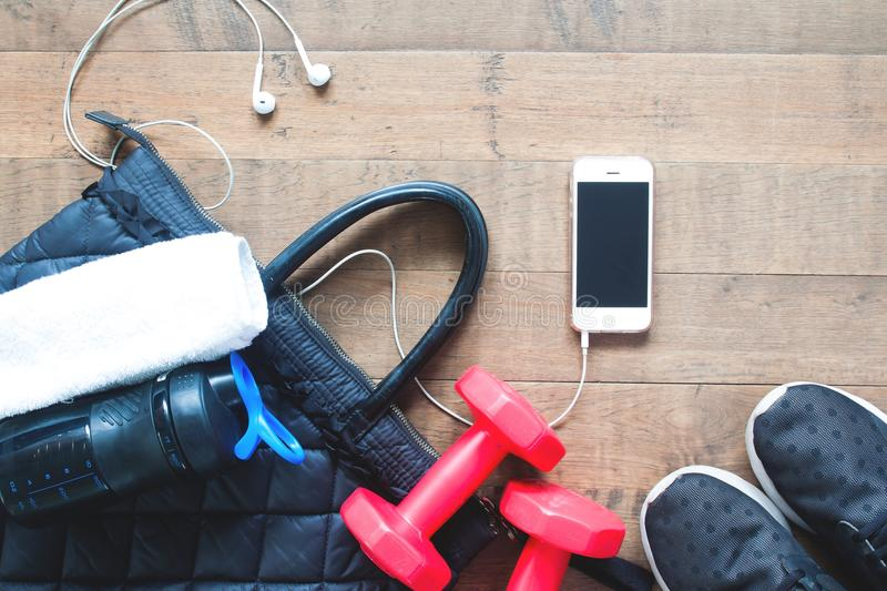 Flat lay of mobile phone, water bottle, towel and red dumbbells on wood stock photo