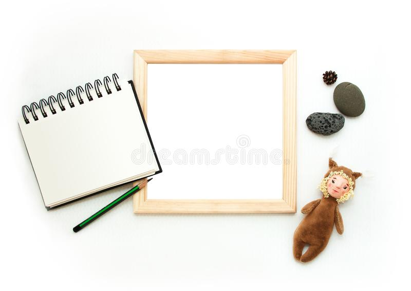 Flat lay mock up, top view, wooden frame, toy squirrel, pencil, note pad, stones. Interior layout, square poster mockup. royalty free stock photography