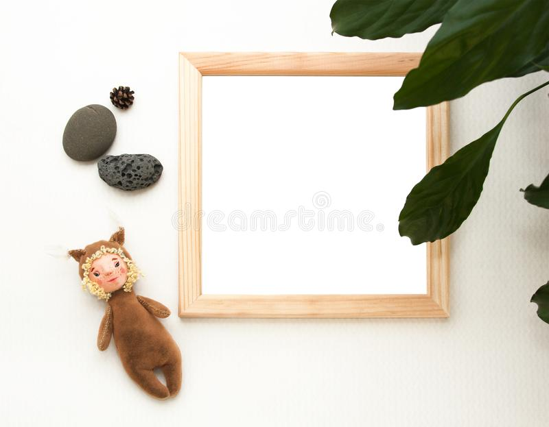 Flat lay mock up, top view, wooden frame, toy squirrel, plant, stones. Interior layout, square poster mockup, wood frame. stock photo