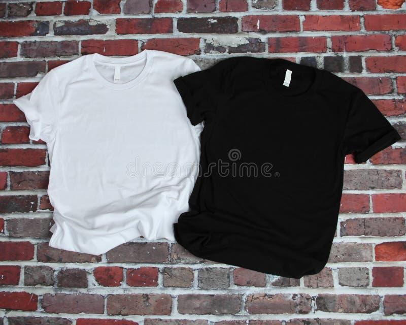 Flat lay mockup of white tshirt and black tshirt on brick background stock photos