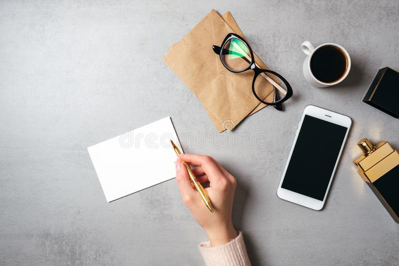Flat lay modern minimal home workspace with hand of woman writing text on blank paper card, glasses, kraft envelope, coffee cup,. Perfume bottle, smartphone royalty free stock photos