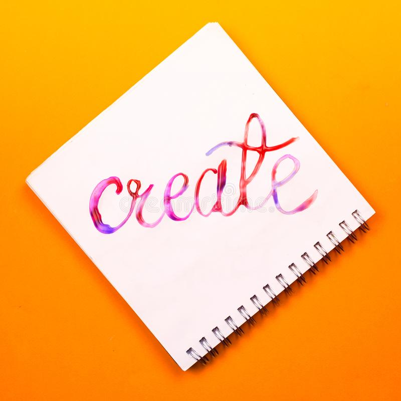 Flat lay of a notebook with colorful hand lettered sign `Create`. Concept of creativity or education royalty free stock image