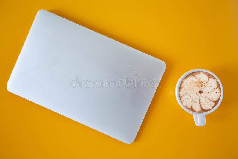 Flat lay Notebook placed on a color table with a cup of coffee,office desk table with laptop and supplies,Top view with copy space stock image