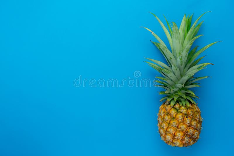 Flat lay object the fresh pineapple on modern rustic blue paper wallpaper. stock photos